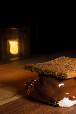 Smore on a wood table with a camping lantern behind