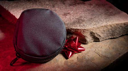 Black nylon tactical bag on rocks with a red Christmas bow 版權商用圖片