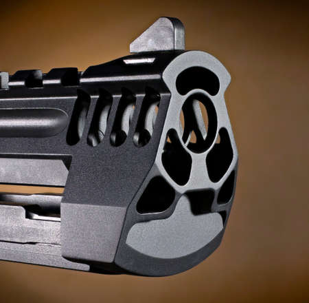 Semi automatic handgun muzzle with a brown background