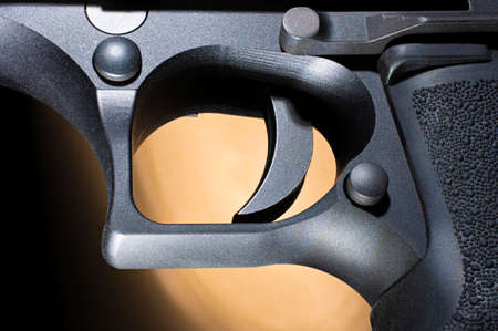 Semi automatic pistol trigger with a brown and black background