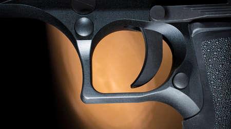 Trigger on a semi auto handgun with a dark background