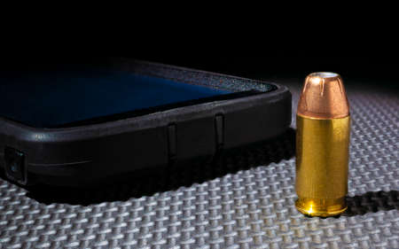 Hollow point cartridge next to a cell phone on a black background