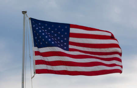 American flag waving in the breeze with clouds and sky behind