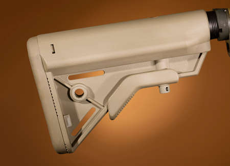 AR-15 adjustable stock that is brown on a beige background