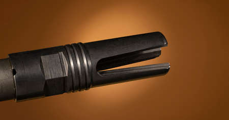 Flash hider on an assault rifle barrel with a brown background