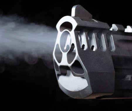 Stream of smoke flowing out of a handgun barrel on a black background 版權商用圖片