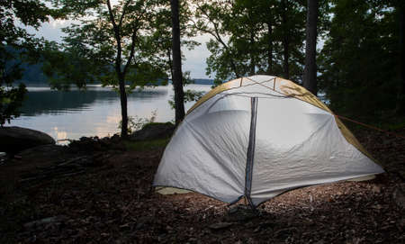Hiking tent lit as dusk arrives at Badin Lake in North Carolina
