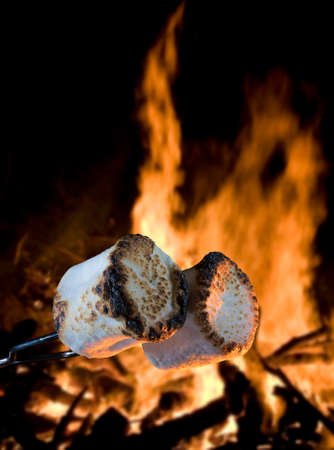 Two marshmallows being roasted over a campfire to make smores 版權商用圖片