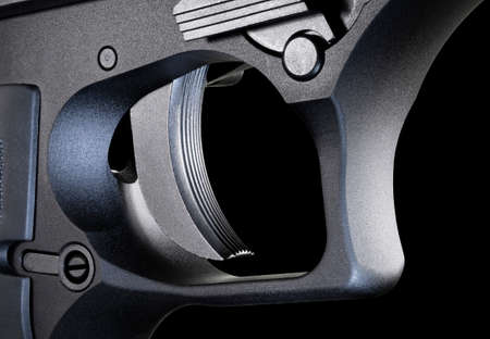 Trigger for an automatic pistol on a black background 版權商用圖片