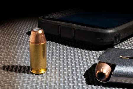 Smart phone next to ammunition and a pistol magazine