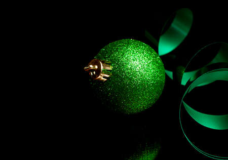 Sparkling green Christmas ornament and ribbon on a black background