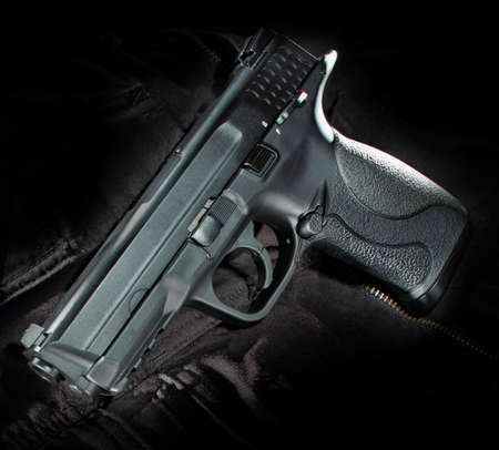 Semi automatic handgun with polymer frame on black material