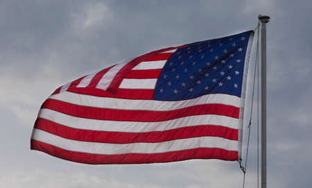 American flag folding over slightly in the breeze with clouds behind