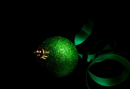 Sparkling Christmas ornament and green ribbon on a dark background Stock Photo