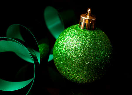Sparkling green Christmas ornament and ribbon on black