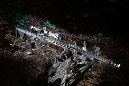 High powered camouflage bolt action rifle and scope in a forest Archivio Fotografico - 135265763