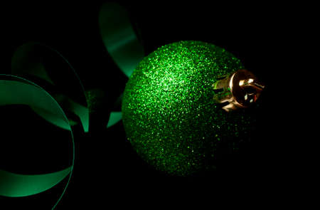 Green ribbon and Christmas ornament on a black background