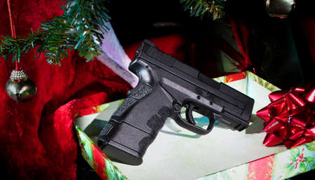 Handgun still in a box under a Christmas tree Archivio Fotografico - 136163452