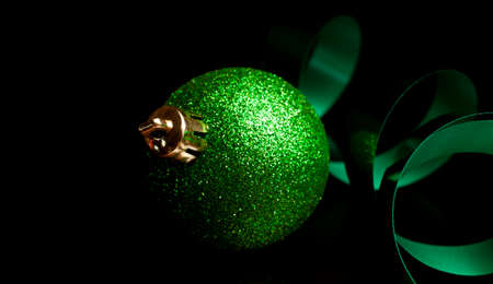 Shiny green Christmas ornament and ribbon on a black background