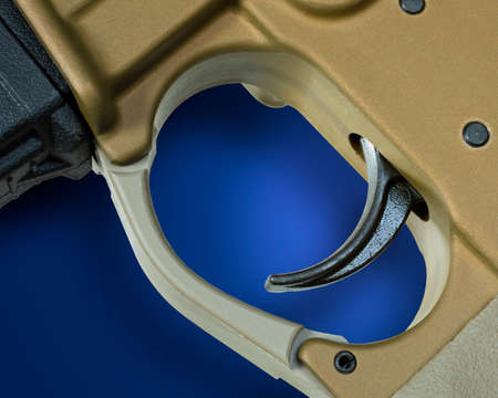 Trigger from an AR-15 assault rifle with shadown on blue Archivio Fotografico - 136163497