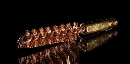 Wire brush for cleaning a gun of twenty seven caliber on a black background