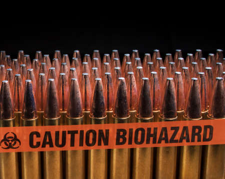 Line of rifle cartridges with biohazard tape in front and room on top for text