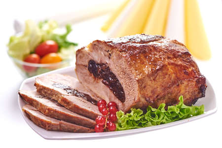 Roast pork with prunes on blurred background, close-up.