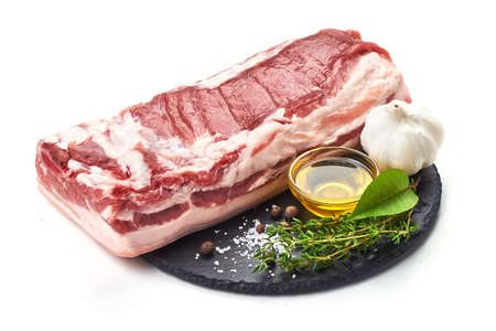 Raw pork meat with spices and oil, served on the slate plate, isolated on white background.