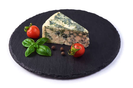 Wedge of soft blue cheese with mold and cherry tomatoes with basil leafs on a slate slab, isolated on white background.