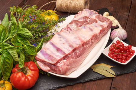 Raw pork meat on a slate stone plate with spices, colorful tomatoes and red currant on a wooden rustic background