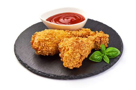 Breaded crispy fried chicken legs with ketchup, isolated on white background.