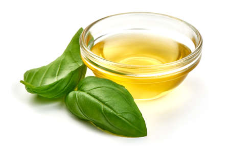 Olive or vegetable oil with basil leaves, isolated on white background Stock Photo
