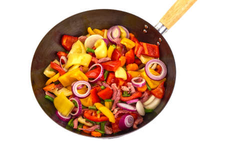 Fried vegetables in a frying pan, isolated on white background.