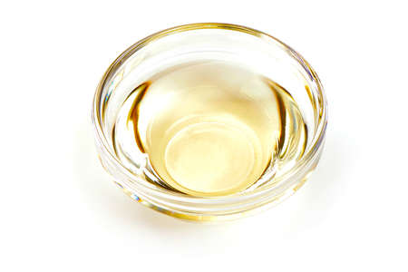 Apple vinegar in glass bowl closeup, isolated on white background.