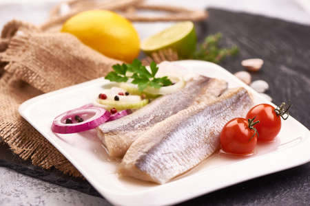 Delicious Atlantic salted herring with onion and tomatoes on the slate shale background. Rustic style
