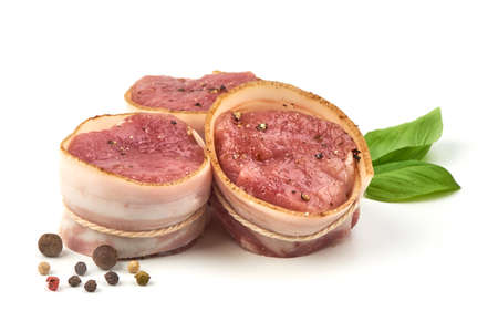 Raw Pork medallions wrapped in bacon with basil leaves and peppercorns, isolated on white background