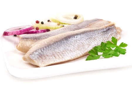 Fillet of salted marinated Atlantic herring with onion and parsley on a white plate, isolated on white background 版權商用圖片