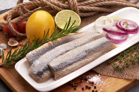 Delicious Atlantic salted herring with onion on the cutting board. Rustic style 版權商用圖片