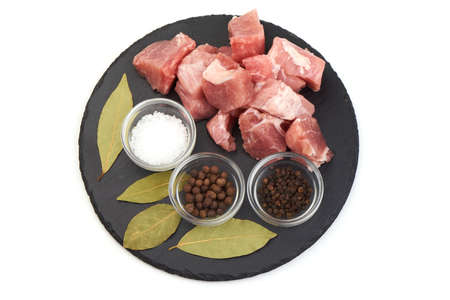Raw pork meat with spices on a shale slate plate, isolated on white background 版權商用圖片