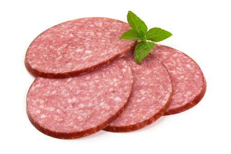 Dry salami sausage slices with basil leaves, isolated on white background