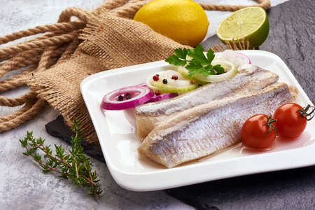 Delicious Atlantic salted herring with onion on the slate shale background. Rustic style