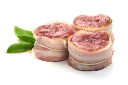 Raw Pork medallions wrapped in bacon with basil leaves, isolated on white background 版權商用圖片
