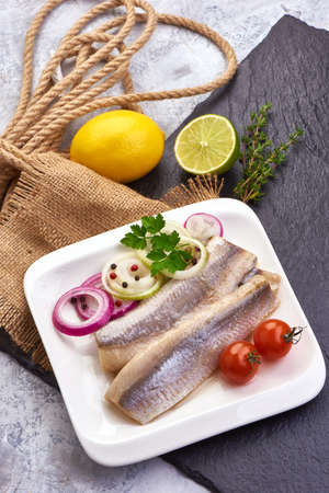 Delicious Atlantic salted herring with onion on the slate shale background. Rustic style. Top view
