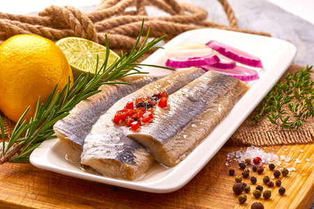 Atlantic Marinated herring fillet with pepper, tomatoes, herbs, onion and lemon on white plate on cutting board