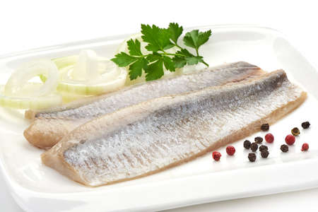 Fillet of salted marinated Atlantic herring with onion, peppercorns and parsley, isolated on white background.