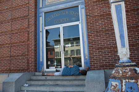 md: Baltimore, MD, USA - July 26, 2011: A street person sleeps on the steps of the Recreation Pier at Fells Point in Baltimore. The building had been featured as police headquarters for NBCs  Homicide: Life on the Street. Editorial