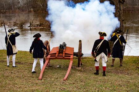 wojenne: Washington Crossing, PA, USA - 25 grudnia 2015: Rekonstruktorów ogień armat kiedy generał Waszyngton i Armii Kontynentalnej osiągnął New Jersey po przekroczeniu rzeki Delaware w łodzi na Boże Narodzenie.