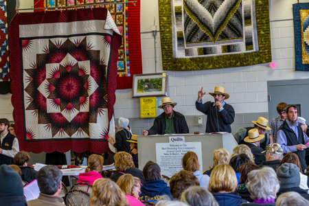 Bart, PA, USA - March 3, 2018: Amish auctioneers sell quilts at the annual Mud Sale at the Bart Fire Company. Stock Photo - 97535631
