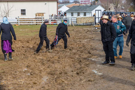 Bart, PA, USA - March 3, 2018: Amish walk through the muddy field at the annual Mud Sale at the Bart Fire Company. 報道画像