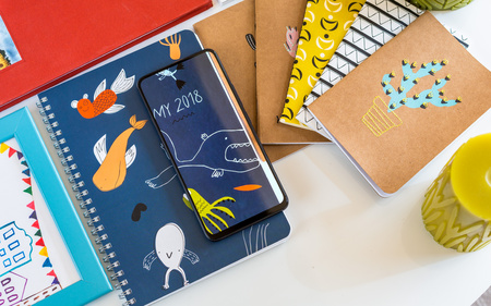 Vivo NEX smartphone on top of colorful notebooks, almost completely blending in